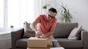 Man opening parcel box with paper knife at home stock footage