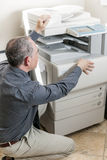 Man opening photocopier in office. Business man opening photocopy machine in office Royalty Free Stock Photography