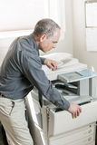 Man opening photocopier in office. Business man opening photocopy machine in office royalty free stock photos