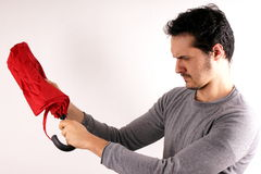 Man opening a red umbrella Stock Photo