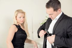 Man opening red wine watched by his wife Royalty Free Stock Photography