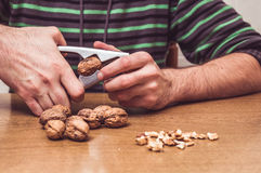 Man opening some walnuts on a table Royalty Free Stock Photos