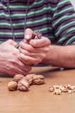 Man opening some walnuts on a table. Hands detail royalty free stock photography