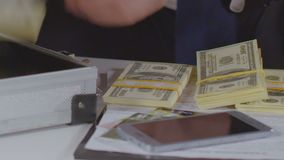Man opening suitcase and taking stacks of money to put on table, financial crime. Stock footage stock video footage
