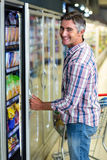 Man opening supermarket fridge. And smiling at the camera Royalty Free Stock Image