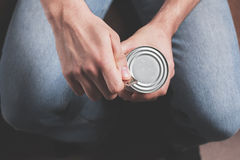 Man opening tin. A man is opening a tin with a tin opener Stock Image