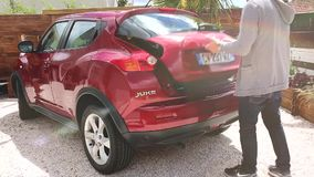 Man Opening The Trunk of His Car. Albi, France - May 21, 2017:  Man Goes To Red Nissan Juke Car Trunk And Load Trunk With Bags stock video footage