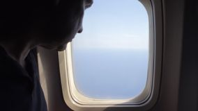 Man opens an airplane window and looks out during air travel. Happy. Man traveling by plane together. Tourism concept. Slow motion. High speed camera shot stock video