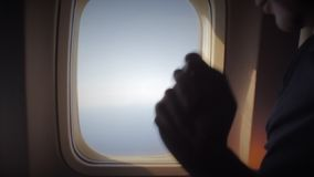Man opens an airplane window and looks out during air travel. Happy. Man traveling by plane together. Tourism concept. Slow motion. High speed camera shot stock footage