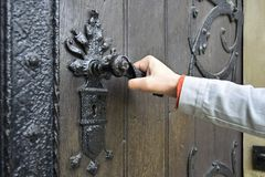 Man opens an ancient wooden door decorated with wrought iron elements royalty free stock image