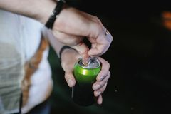 A man opens a can with his hand in close-up stock image