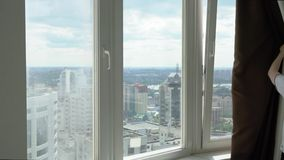 Man opens the curtain on the windows. Overlooking the city stock video footage