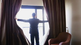 Man opens the curtains stock video footage