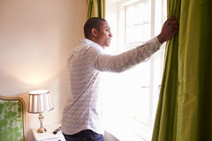 Man opens curtains to look at the view from a hotel window Stock Images