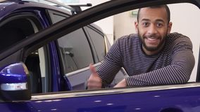 Man opens door of purple crossover. Young black man opening door of purple crossover at the showroom. Handsome african american man smiling for the camera Royalty Free Stock Photography