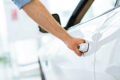 Man opens the door to a new car Stock Photos