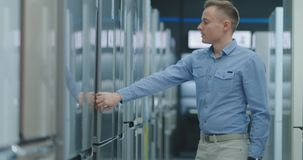 A man opens the door of the washing machine inspect the design and quality before buying in a consumer electronics store. Read the information on the price tag stock video footage