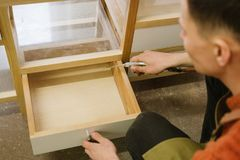 Man opens a drawer in the table. In the carpentry workshop stock images
