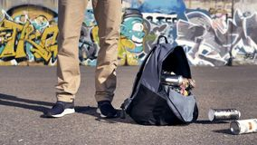 A man opens his hand with a backpack full of spray paints. A view on male legs as a backpack with spraint paints falls down stock video footage