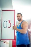 Man opens locker door in gym Stock Image