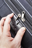 Man opens numbered lock on suitcase Royalty Free Stock Image