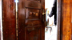 Man opens old door and enters bright room stock video footage