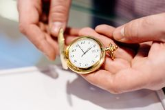 Man opens retro styled pocket watch. Man opens retro styled vintage gold coloured pocket watch Royalty Free Stock Photography