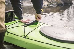 The man opens a sealed hatch cover for things in the kayak that Stock Images