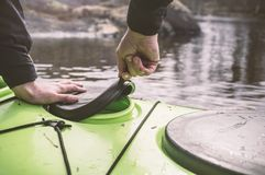 The man opens a sealed hatch cover for things in the kayak that Stock Photo