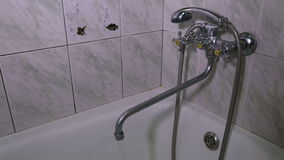 The man opens the tap water in the bathroom. And water begins to flow stock footage