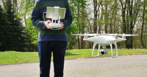 Man Operates Drone in Open Field. A man operates a small UAV in an open field stock video