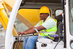 Man operates excavator. African american man operates excavator on building site Stock Images