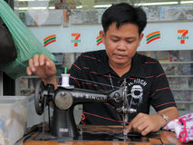 Man Operates Sewing Maching in Textiles Shop Royalty Free Stock Images