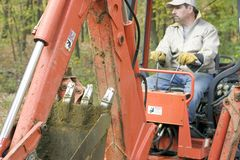 Man Operating Backhoe Stock Photo