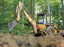 Man operating backhoe. Man removing tree roots with a backhoe stock photography