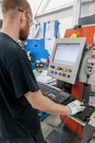 Man operating CnC machine Stock Photo