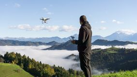 Man operating drone flying or hovering by remote control with beautiful foggy landscape in the background stock photos