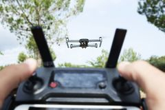 Man operating a drone in a natural landscape Stock Photo