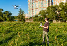 Man operating a drone quad copter in city park Stock Photo