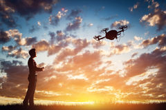 Man operating a drone at sunset. Royalty Free Stock Images