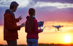 Man operating of flying drone at sunset Stock Photos