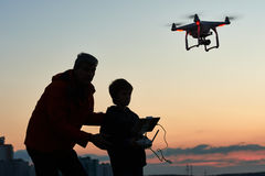 Man operating of flying drone at sunset. Man with child operating drone flying or hovering by remote control in sunset Stock Photo