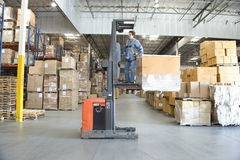 Man Operating Forklift Truck In Warehouse royalty free stock image