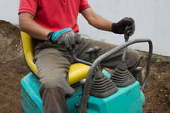 Man operating the gearshift of a mini digger. In the garden royalty free stock photo