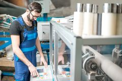 Man operating machine which makes paper tubes. At the manufacturing stock photos
