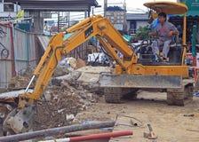 Man is operating power shovel in Bangkok, Thailand. Bangkok, Thailand - May 11, 2015: man is operating power shovel in Bangkok, Thailand Royalty Free Stock Images