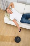 Man operating robotic vacuum cleaner with remote control Stock Photography