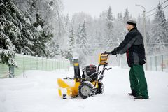 A man operating snow blower Stock Image