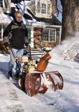 Man Operating Snow Blower. To clear driveway Stock Photos