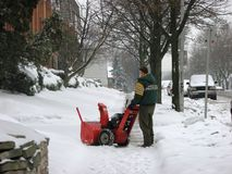 Man operating snow blower to clear driveway Stock Photo